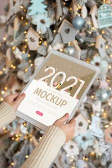 Personne tenant la tablette avec le nouvel an devant les décorations de noël