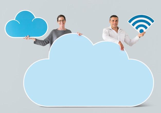 Personnes détenant des icônes de nuage et de la technologie