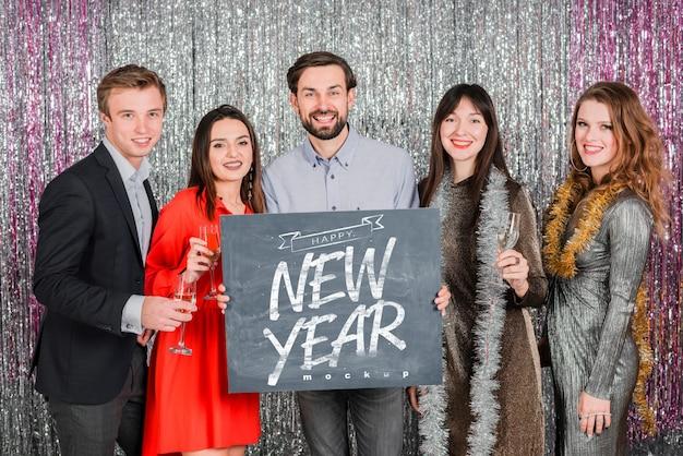 Personnes tenant un tableau pour le nouvel an