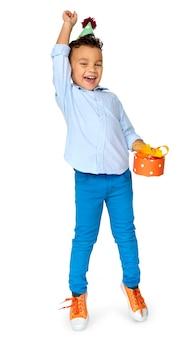 Petit garçon avec un cadeau party hat studio portrait