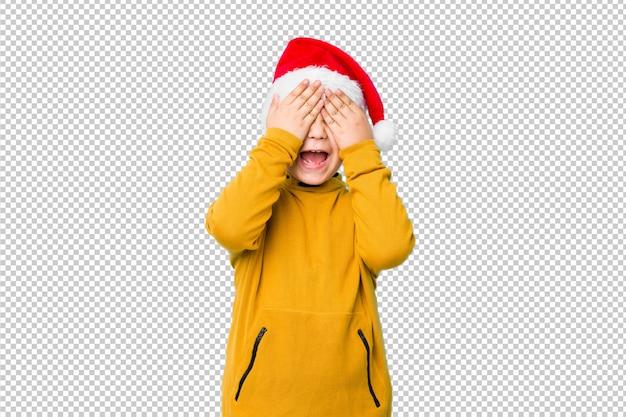 Petit garçon célébrant le jour de noël portant un bonnet de noel couvre les yeux avec les mains, sourit largement attendant une surprise.