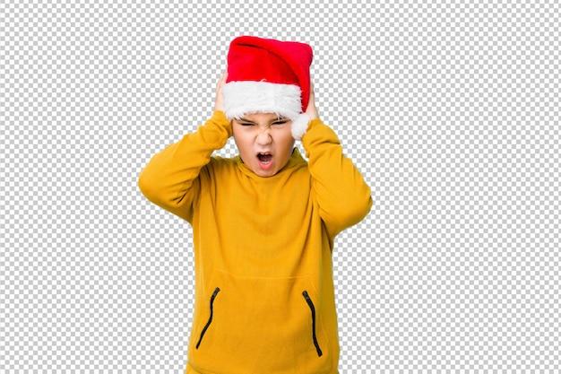 Petit garçon fête le jour de noël avec un bonnet de noel couvrant les oreilles avec les mains en essayant de ne pas entendre un son trop fort.