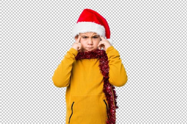 Petit garçon fête le jour de noël avec un bonnet de noel isolé concentré sur une tâche, gardant les index pointés vers la tête.