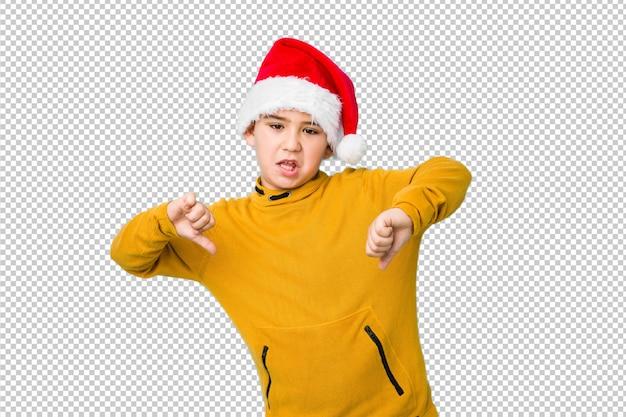 Petit garçon fête le jour de noël avec un bonnet de noel montrant le pouce vers le bas et exprimant l'aversion.