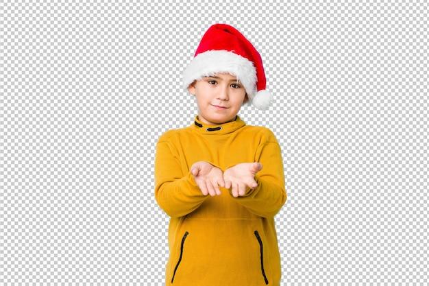 Petit garçon fête le jour de noël avec un bonnet de noel tenant quelque chose avec des paumes, offrant à la caméra.