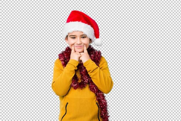 Petit garçon fête le jour de noël, coiffé d'un bonnet de noel isolé doutant entre deux options.