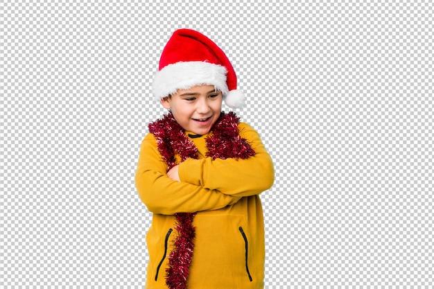 Petit garçon fête le jour de noël coiffé d'un bonnet de noel rire et s'amuser.