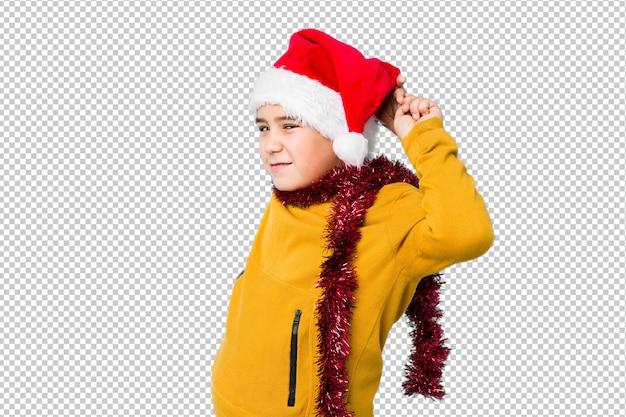 Petit garçon fête le jour de noël portant un bonnet de noel isolé étirement des bras, position détendue.