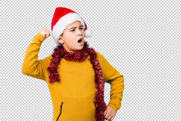 Petit garçon fête le jour de noël portant un bonnet de noel isolé levant le poing après une victoire, concept gagnant.