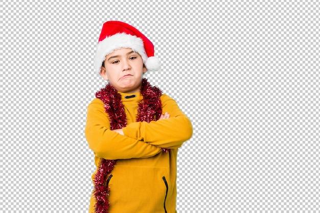 Petit garçon fête le jour de noël portant un bonnet de noel malheureux à la recherche à huis clos avec une expression sarcastique.