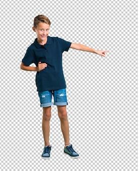 Petit garçon montrant un doigt sur le côté et présentant un produit