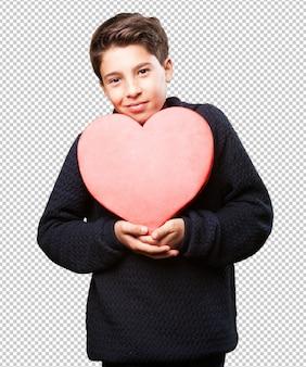 Petit garçon tenant un coeur