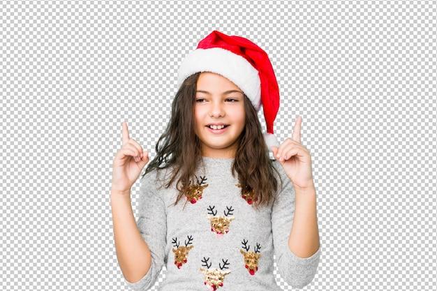 Petite fille célébrant le jour de noël indique avec les deux doigts devant montrant un espace vide.