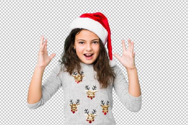 Petite fille célébrant le jour de noël recevant une agréable surprise, excitée et levant les mains.