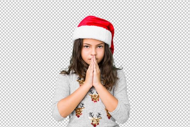 Petite fille célébrant le jour de noël, tenant par la main pour prier près de la bouche, se sent confiante.