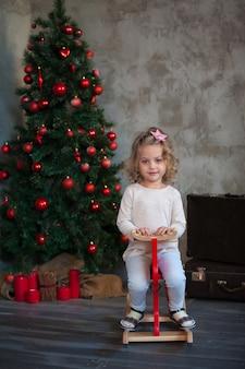 Petite fille à côté de l'arbre de noël, avec un chandail de maquette pour votre conception
