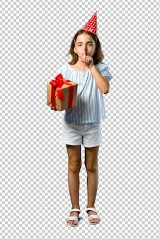 Petite fille à une fête d'anniversaire tenant un cadeau montrant un signe de fermeture bouche et geste de silence