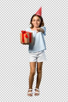 Petite fille à une fête d'anniversaire tenant un cadeau pointe le doigt vers vous