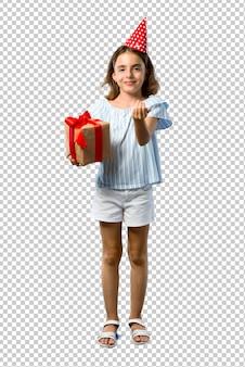 Petite fille à une fête d'anniversaire tenant un cadeau présentant et invitant à venir