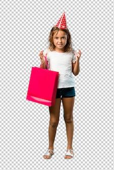 Petite fille à une fête d'anniversaire tenant un sac-cadeau agacé énervé, en colère, geste furieux