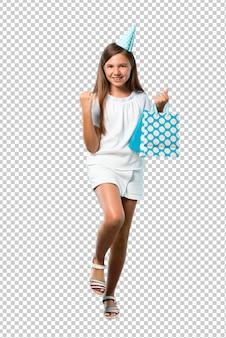 Petite fille à une fête d'anniversaire tenant un sac cadeau célébrant une victoire