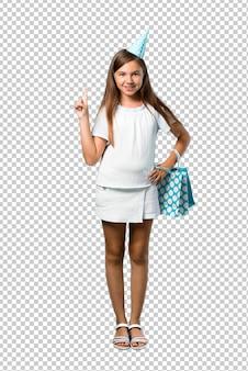 Petite fille à une fête d'anniversaire tenant un sac cadeau comptant le signe numéro un
