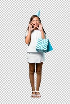 Petite fille à une fête d'anniversaire tenant un sac-cadeau criant avec la bouche grande ouverte