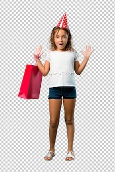 Petite fille à une fête d'anniversaire tenant un sac cadeau avec une expression faciale surprise et choquée
