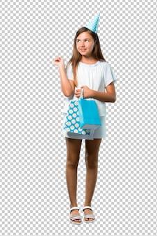 Petite fille à une fête d'anniversaire tenant un sac cadeau pointant avec l'index une excellente idée