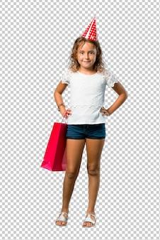 Petite fille à une fête d'anniversaire tenant un sac cadeau posant avec les bras à la hanche