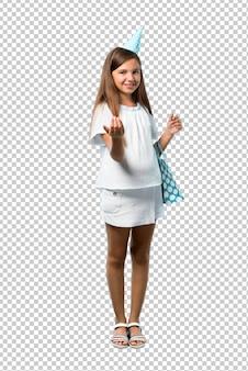 Petite fille à une fête d'anniversaire tenant un sac cadeau présentant et invitant à venir