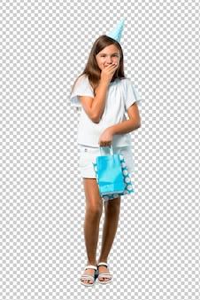 Petite fille à une fête d'anniversaire tenant un sac cadeau en riant