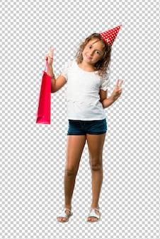 Petite fille à une fête d'anniversaire tenant un sac cadeau souriant et montrant le signe de la victoire