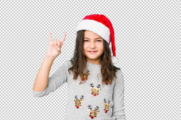 Petite fille fête le jour de noël montrant un geste de cornes comme un concept de révolution.