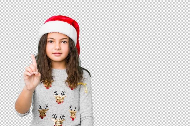 Petite fille fête le jour de noël, montrant le numéro un avec le doigt.
