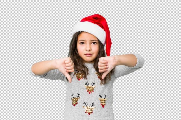 Petite fille fête le jour de noël montrant le pouce vers le bas et exprimant l'aversion.