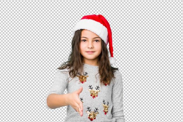 Petite fille fête le jour de noël, qui s'étend de la main à la caméra en geste de voeux.