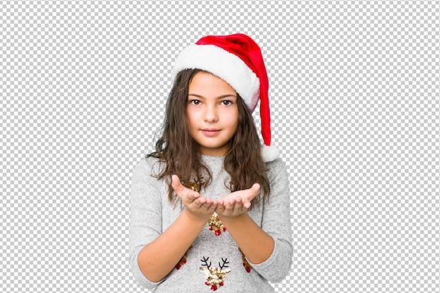 Petite fille fête le jour de noël tenant quelque chose avec des paumes, offrant à la caméra.