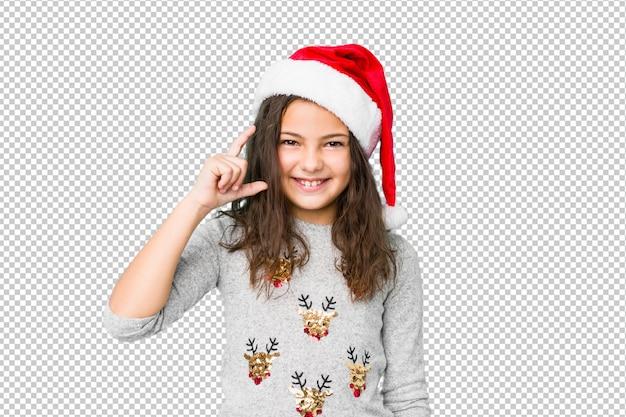 Petite fille fête le jour de noël tenant quelque chose de petit avec les index, souriant et confiant.