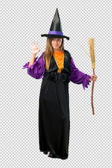Petite fille habillée comme une sorcière pour les vacances d'halloween montrant un signe ok avec les doigts