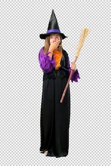 Petite fille habillée en sorcière pour les vacances d'halloween couvrant la bouche avec les mains