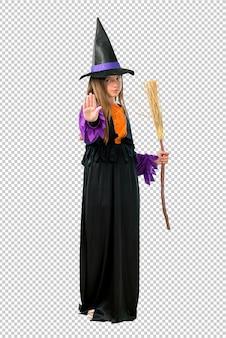 Petite fille habillée en sorcière pour des vacances d'halloween faisant un geste d'arrêt avec sa main