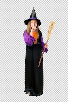 Petite fille habillée en sorcière pour des vacances d'halloween montrant un signe de fermeture de la bouche