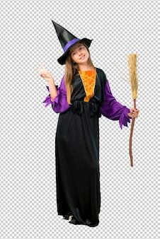 Petite fille habillée en sorcière pour les vacances d'halloween en souriant et en montrant le signe de la victoire