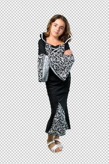 Petite fille habillée en vampire pour les vacances d'halloween en gardant les bras croisés