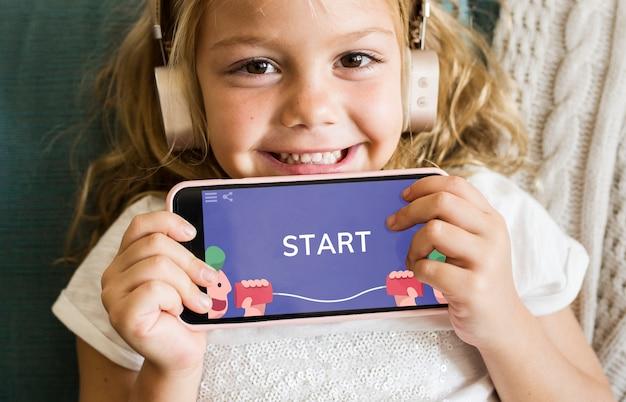 Petite fille jouant à un jeu mobile