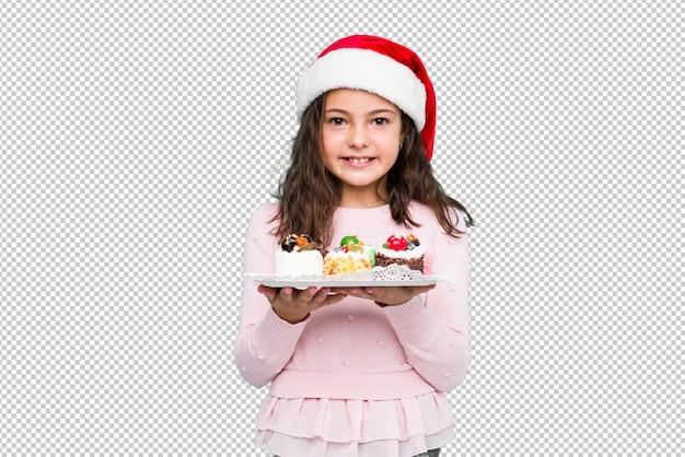 Petite fille tenant des bonbons célébrant le jour de noël