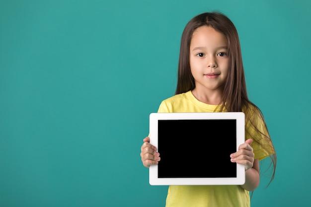 Petite fille tenant une tablette vierge