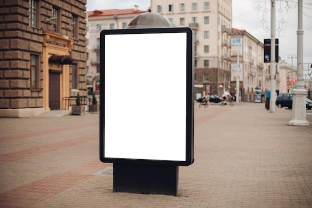 Photo d'un grand panneau d'affichage qui se tient dans la rue, où beaucoup de gens marchent