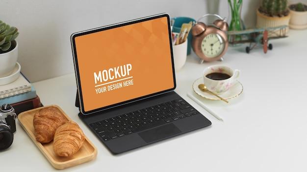 Photo recadrée de bureau à domicile avec tablette numérique, décorations, croissant et café